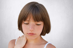 Close Up Of Attractive Little Child With Freckles And Dark Short Hair Keeping Her Hand On Neck, Looking Seriously Down, Having Tho