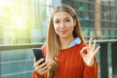 Free Close Up Of Beautiful Autumn Woman Holding Smart Phone Doing Ok Sign At The Camera. Smiling Cheerful Satisfied Young Woman Using Royalty Free Stock Photos - 161728128