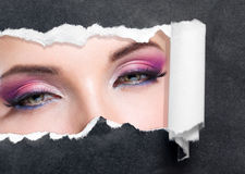 Close Up Of Female Eyes With Bright Make-up On Torn Black Paper Stock Photo