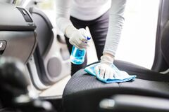 Free Close Up Of Female Wearing Surgical Gloves While Cleaning Car Interior With Disinfection Liquid Sprayer And Microfiber Cloth Royalty Free Stock Image - 182813316