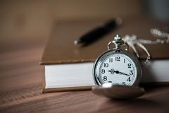Close Up Of Golden Pocket Watch Lean On Pile Of Book. Stock Image