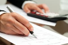 Close Up Of Hand With Pen On Accounting Document. Royalty Free Stock Images