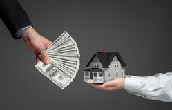 Close Up Of Hands Giving House Model For Money Stock Photography