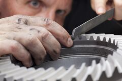 Free Close-up Of Hands Of A Mechanic Repairing A Cog Wheel With A Rasp Royalty Free Stock Photos - 193308048