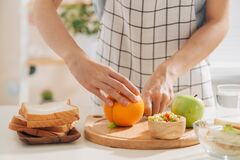 Free Close-up Of Lady Arms Cutting Orange By Knife Into Slices Royalty Free Stock Images - 168857949