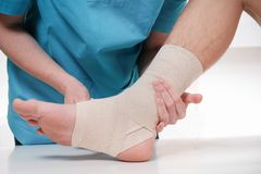 Free Close-up Of Male Doctor Bandaging Foot Of Female Patient Royalty Free Stock Image - 112927286