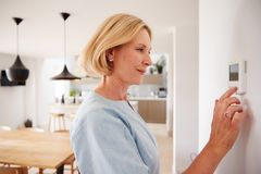 Free Close Up Of Mature Woman Adjusting Central Heating Temperature At Home On Thermostat Stock Photo - 163726580