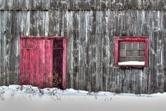 Free Close Up Of Old Gray Wood Planks Barn In A Snow Field With Red Door And Red Window Stock Photos - 169888683