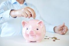 Free Close Up Of Old Man Putting Coins Into Piggybank Stock Image - 51495181