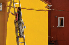 Close-up Of Painter Painting Wall Of House Of Yellow In Burano. Royalty Free Stock Photography