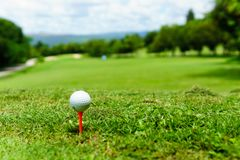 Free Close Up Of White Golf Ball On Orange Tee On Green Grass With Blue Sky And Cloud And View Of Mountain Background In Sunny Day. Stock Image - 99362011