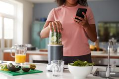 Free Close Up Of Woman Using Fitness Tracker To Count Calories For Post Workout Juice Drink She Is Making Stock Image - 157270801