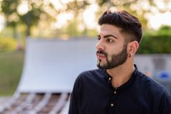 Free Close Up Of Young Handsome Indian Man Thinking Against Skateboar Royalty Free Stock Images - 116489169