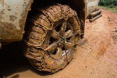 Close up of off road car tire with chain on it Royalty Free Stock Photo