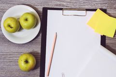 Close up of office accessorise: clipboard, a plate of apples, blank notepad on a wooden background. Weight loss starving dieting s. Limming concept Royalty Free Stock Image