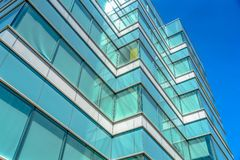 Close up of an office building exterior against blue sky on a sunny day. Roller blinds on the windows provide shade and privacy to the rooms royalty free stock photo