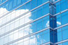 Close up of office building with reflection of blue sky and clou Stock Images