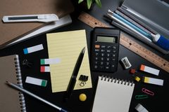 Close up of office business supplies on black background in studio. Basic and classic office business supplies. Set of school supplies or business supplies Stock Photography