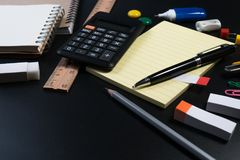 Close up of office business supplies on black background in studio. Basic and classic office business supplies. Set of school supplies or business supplies stock images