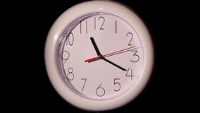 Close up of an office clock on black background. With clipping path. slow motion stock video footage