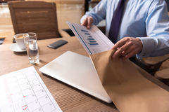 Close up of office documents being put in the envelope. Sending the report. Close up of office documents with statistical data being in the hands of a man while Royalty Free Stock Image