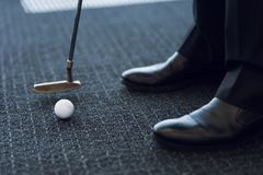 Close up. Office golf. Golf club and golf ball on a gray carpet Royalty Free Stock Photos