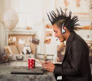 Close up of office punk man, wearing a suit with a crest hair style, using his tablet and headphones to work in the. Office, in a blurred background stock images