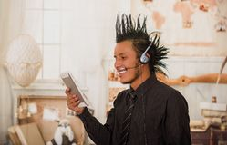 Close up of office punk man, wearing a suit with a crest, with headphones in his head and using his tablet in the office. In a blurred background Royalty Free Stock Image