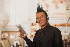 Close up of office punk man, wearing a suit with a crest, with headphones in his head and using his tablet in the office. In a blurred background Royalty Free Stock Images