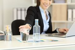 Office worker reaching a glass of water. Close up of an office worker hand reaching a glass of bottled water royalty free stock images