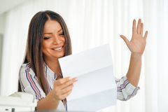 Happy entrepreneur woman reading good news in a letter. Close-up of an office worker. Woman, enjoying the good news in writing. An euphoric girl is happy after Royalty Free Stock Photography