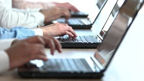 Close up office workers hands typing. Office clerks working with laptops, close up stock footage