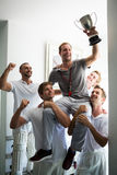 Close up oh happy team with cup standing in locker. Room after match royalty free stock photo
