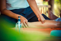 Close up of Oil Massage Spa at leg by Hand in tropical garden for wellness and healthy background Stock Photos