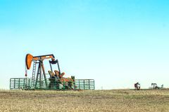 Close--up of oil well pump jack out in a field enclosed in a metal cattle fence with two other pumping wells in the distance all stock photography
