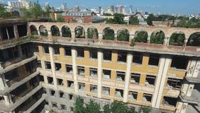 Close-up of old, abandoned building with young woman in pink dress dancing on the highest floor. Footage. Aerial view stock video footage