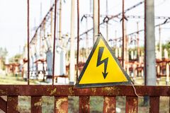 Close-up old aged rusty triangle metal plate with High voltage warning sign. Power station with transformers and electricity stock photo