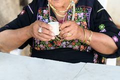 Close up of old arabian woman hands with traditional arabian dress and jewelry holding cup of coffee. stock image