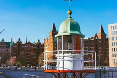 Close up of old beacon lighthouse and red brick building in background, Hafencity - Speicherstadt in Hamburg, Germany.  Royalty Free Stock Photos