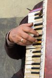 Close Up of Old Beggar Woman Playng a Dirty Accordion in the Street. On Blur Background royalty free stock images
