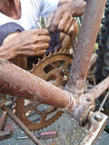 Close up of old bicycle frame and crank with hands of repairman Royalty Free Stock Images