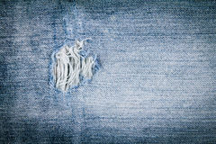 Close up old blue jean texture with torn hole Royalty Free Stock Images