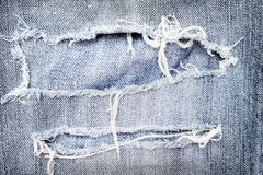 Old blue jeans with ripped texture , hole and white threads destroyed patterns on denim for background royalty free stock photography