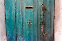 Close up of old blue teal painted door with round door handle, knocker. And letter box royalty free stock images