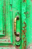 Close-up of old bronze door knob. Close up of old bronze door knob on obsolete green door Royalty Free Stock Image