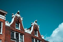 Close-up of old building facade and roof decoration against blue sky in Amsterdam. Architectonic Details Northern Netherlands.  royalty free stock images