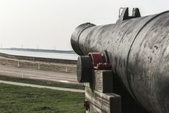 An old cannon standing on a grass field royalty free stock photo