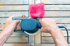 Close-up of old carpenter`s hands working with electric sander Stock Photos
