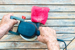 Close-up of old carpenter`s hands working with electric sander. Polishing old color from wooden table Royalty Free Stock Photo