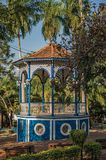 Close-up of an old colorful gazebo in the middle of verdant garden full of trees, in a sunny day at São Manuel. stock image